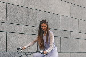 Beautiful young woman getting to work by bike