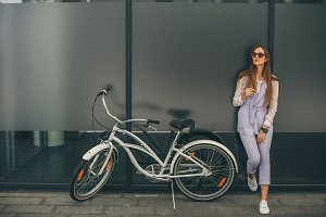 Beautiful young smiling woman standing near her vintage bicycle