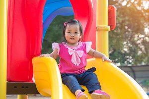 Toddler girl playing on a slide
