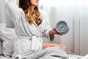 girl in the morning in bed with clock