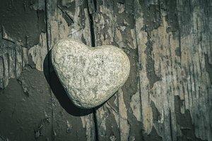 Stone heart shape on wood.