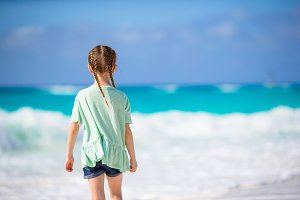 Back view of adorable little girl at beach