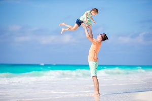 Little girl and young father having fun during tropical beach vacation