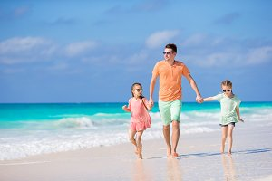 Family walking on white tropical beach on caribbean island