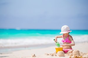 Adorable little girl playing with beach toys on the white beach