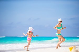 Little adorable girl and young mother haveing fun at tropical beach