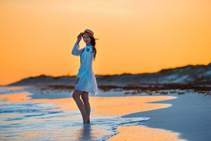 Young beautiful woman on tropical seashore in sunset. Happy girl in dress in the evening on the beach