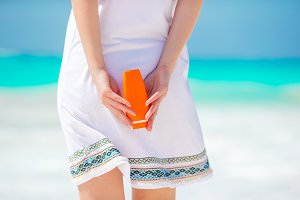Closeup suncream bottle in female hands on the beach