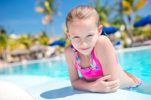 Portrait little girl having fun in outdoor swimming pool