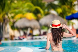 Beautiful young woman relaxing in swimming pool. Back view of girl in outdoor pool at luxury hotel