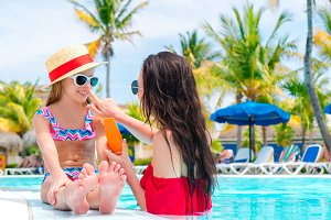 Young mother applying sun cream to kid nose in swimming pool