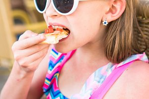 Portrait of little girl eating pizza in outdoor cafe at dinner