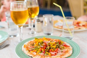 Pizza with mozzarella cheese, olive, fresh tomato and pesto sauce. Served at restaurant table with two beers