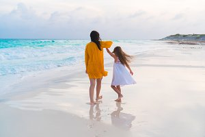 Little adorable girl and young mother at tropical beach in warm evening