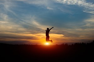 Silhouette of a cheerful man at sunset. Leap at sunset.