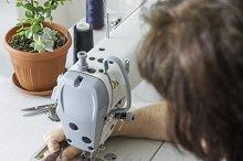 Women sew on sewing machine