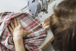 Women sew on sewing machine
