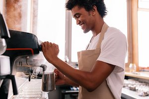 Happy young man preparing coffee