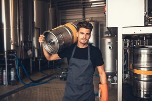 Male brewer carrying metal container
