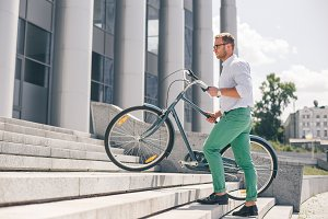 Young stylish businessman carrying bicycle up steps