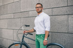 Confident business man with bike. Confident young handsome man in shirt