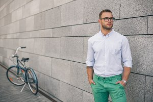 Full length of handsome young businessman with his bicycle.