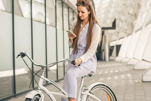 Beautiful young woman siting on bicycle near the business center