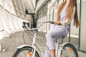 Woman with vintage bike. Side view of cheerful young woman in sunglasses