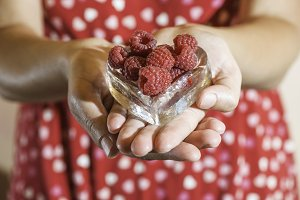 Woman holding a cup of raspberries
