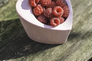 Raspberries in a bowl on wood