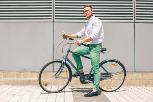 Pensive casual businessman going to work by bicycle