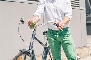 stylish hipster posing next to his bicycle with lemonade