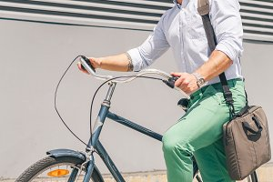 stylish businessman going to work by bike with laptop bag on shoulder