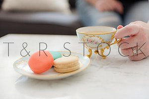 Woman holding Tea Cup, Macarons