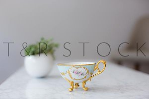 Gold Tea Cup with White Round Plant