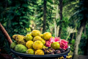 Mixed tropical fruits in the basket on a rainforest background. Bali island, Indonesia.