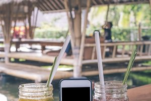 Glasses of strawberry and mango juices with soda on a wooden table and smartphone with black screen. Tropical cafe background. Bali island.