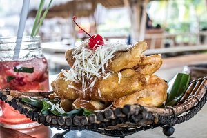 Fried banana desser, pisang goreng keju, indonesian dessert with batter fried bananas dusted with powdered sugar and cheese. Bali.