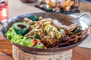 Mie goreng, mi goreng, indonesian fried noodles with beautiful decoration on a wooden table. Bali island.