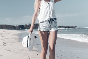 Young sexy woman with white hat walking on white sand beach a tropical Bali island at sunny day. Ocean cost.