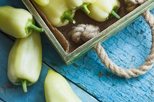 Green fresh bell peppers in the wooden tray