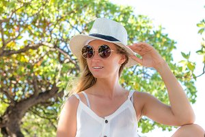 Portrait of young beautiful sexy woman with white hat posing on the tropical beach tree, Bali island.