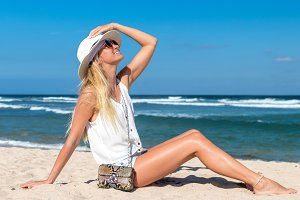 Fashion woman with luxury snakeskin python bag on the beach of tropical island Bali, Indonesia.