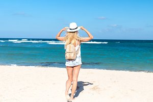 Young sexy woman with white hat and luxury snakeskin python backpack walking on white sand beach a tropical Bali island at sunny day. Ocean cost.