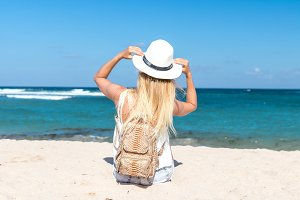 Young sexy woman with white hat and luxury snakeskin python backpack sitting on white sand beach a tropical Bali island at sunny day. Ocean cost.