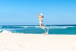 Young sexy woman with white hat and luxury snakeskin python backpack jumping on white sand beach a tropical Bali island at sunny day. Ocean cost.