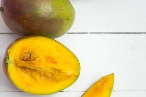 Mango fruits closeup on white wooden background,