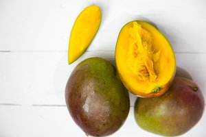 Mango fruits closeup on white wooden background,