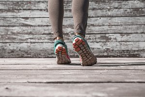 female legs in sneakers on a wooden background