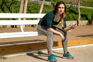 The girl in sportswear on a bench listening to music